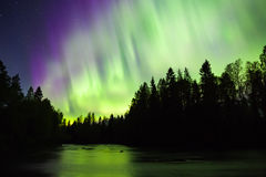 Colorful northern lights (Aurora borealis) in the sky. By the river royalty free stock images