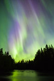 Colorful northern lights (Aurora borealis) in the sky. By the river royalty free stock photo