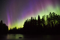 Colorful northern lights (Aurora borealis) in the sky. By the river stock images