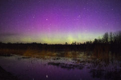 Colorful Northern Lights with Reflection on Water. Powerful northern lights over night sky in Saaremaa Estonia. Aurora borealis was bright and with many colors Royalty Free Stock Images