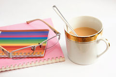 Colorful notebook glasses and coffee cup. The Colorful notebook glasses and coffee cup Royalty Free Stock Images