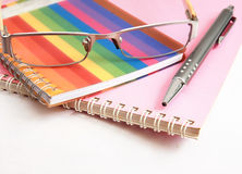 Colorful notebook pen and glasses on white Stock Images