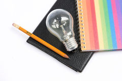 Colorful notebook with pencil and light bulb. The Black notebook with pencil and light bulb Royalty Free Stock Photo