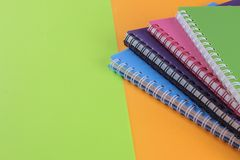 colorful notebooks on a bright green and orange background. stationery. with place for inscription stock image