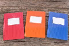 Colorful notebooks on wooden background Stock Photography