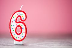 Colorful number 6 birthday cake candle on a pink background stock image
