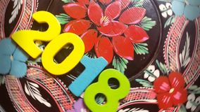 The colorful number 2018 revolves on a round wooden disk with painted flowers ornament stock footage