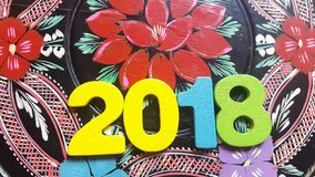 The colorful number 2018 revolves on a round wooden disk with painted flowers ornament stock video footage