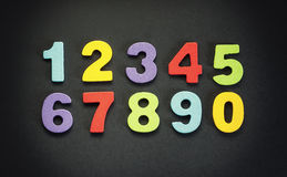 Colorful Numbers. Wooden numbers in various colors, in two rows on black background stock photo