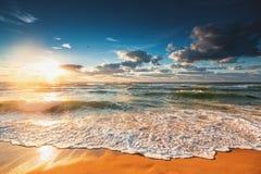 Colorful ocean beach sunrise with deep blue sky and sun rays. Beautiful cloudscape over the sea, sunrise shot Stock Photos