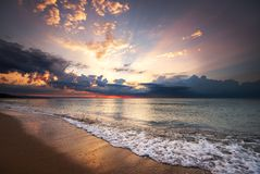 Colorful ocean beach sunrise with deep blue sky and sun rays. Golden sands Stock Image