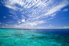 Colorful ocean and sliding clouds. Colorful turquise ocean and sliding clouds in deep blue sky Stock Photo