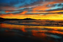 Colorful ocean sunrise at Nahoon Beach. Colorful, cloudy ocean sunrise with reflection in wet sea-sand at Nahoon Beach, East London, South Africa Royalty Free Stock Images