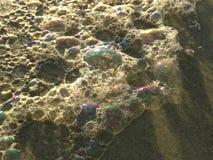 Colorful Ocean Wave Foam Bubbles on Beach Sand. Colorful Ocean Wave Foam Bubbles on Beach Sand on Daytona Beach at Daytona Beach Shores, Florida during Sunrise Stock Images