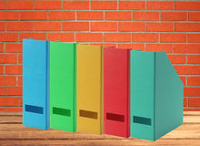 Colorful office folders on wooden table over orange brick wall Stock Images