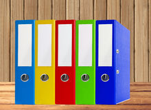 Colorful office folders on wooden table over wooden background Stock Photo