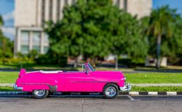 Colorful, old, antique, made over vehicle resembling 1950 American car in Havana, Cuba. In bright pink stock photography