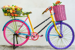 The colorful old bicycle. Flower and fruit in the basket on a colorful bicycle Royalty Free Stock Images