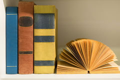 colorful old books on a white wooden book shelf Stock Image