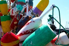 Colorful old buoys by the water in Provincetown Cape Cod with sky and masts of ships in background stock photo