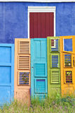 Colorful Old Doors Collection. Collection of colorful old wooden doors in front of blue house with red shutters Royalty Free Stock Image