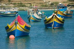 Colorful, old fisher boats are parking in harbor of Marsaxlokk, Malta. Famous Malta attraction, traditional blue and yellow painted old fashioned fisher boats Stock Images