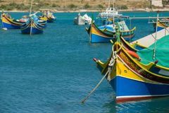 Colorful, old fisher boats are parking in harbor of Marsaxlokk, Malta. Famous Malta attraction, traditional blue and yellow painted old fashioned fisher boats Stock Photography