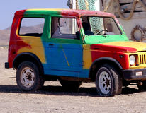 Colorful old off road car. Side view of colorful painted old, off road car with building and desert in background royalty free stock photos