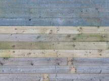 Colorful old rustic wooden plank wall or floor with some of the boards stained blue made of reused timber royalty free stock image