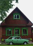 Colorful old wood cottage with green old car royalty free stock image