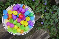 Bowl Full of Eggs. Colorful open plastic eggs in a round big ceramic bowl on a wooden stairs surrounded by flowering ground cover. Close up Stock Photo