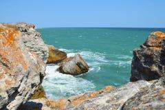 Colorful orange clifs, rocks and green sea Stock Photos