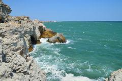 Colorful orange clifs, rocks and green sea Stock Photography