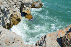 Colorful orange clifs, rocks and green sea Stock Images