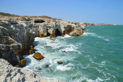 Colorful orange clifs, rocks and green sea Royalty Free Stock Photography