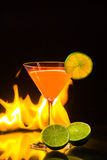 Colorful orange cocktail in nice carroty color to front of a black background and fire. Colorful orange cocktail  in nice carroty color to front of a black Stock Photography