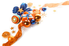 Colorful orange, gold and blue Xmas background. Over white with copyspace in a corner arrangement of baubles, ribbon, star, bow and gifts Royalty Free Stock Image