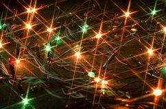 Colorful christmas lights on dark background. Colorful orange green christmas lights star shape on dark background close up Royalty Free Stock Photography