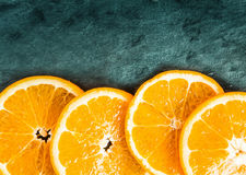 Colorful orange slices on textured slate Royalty Free Stock Images