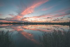 Colorful sunrise over the lake - vintage effect. Colorful orange sunrise over the lake in summer - vintage effect Stock Photo