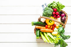 Colorful organic spring vegetables in wicker basket on wood Stock Photography