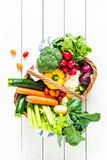 Colorful organic spring vegetables in wicker basket on wood royalty free stock photos