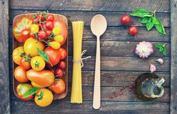 Colorful organic tomatoes in wooden plate with pasta olive oil g. Arlic spices and basil. Fresh red yellow orange and green tomatoes and pasta on wooden stock photography