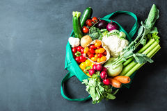 Colorful organic vegetables in green eco shopping bag. Captured from above top view, flat lay. Black chalkboard blackboard as background. Layout with free Stock Photos