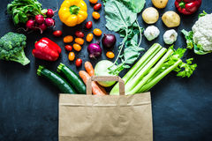 Colorful organic vegetables in paper eco shopping bag. Fresh colorful organic vegetables coming out from paper eco shopping bag - captured from above top view stock images