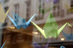 Colorful origami cranes in a store window. Decorative origami cranes in a window Royalty Free Stock Image