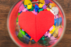 Colorful origami heart in glass. On wood background Stock Photography