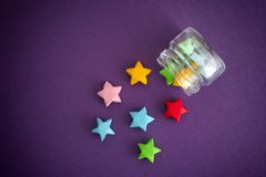Colorful origami lucky stars spilling out of a jar Stock Images