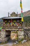 Colorful ornate buddhist stupa. Traditional village entrance in Nepal. Royalty Free Stock Images