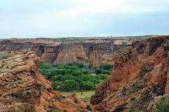 Canyon de Chelly. Colorful outcroppings with greenery and mesa against blue sky at Canyon de Chelly, Arizona Stock Photography